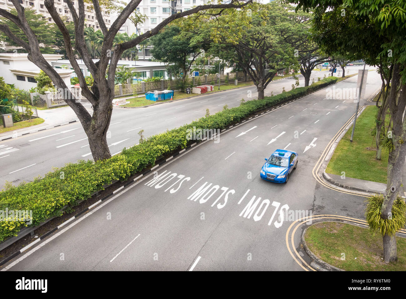 Blue Taxi driving down empty, wide tree lined Singapore Street - Stock Image