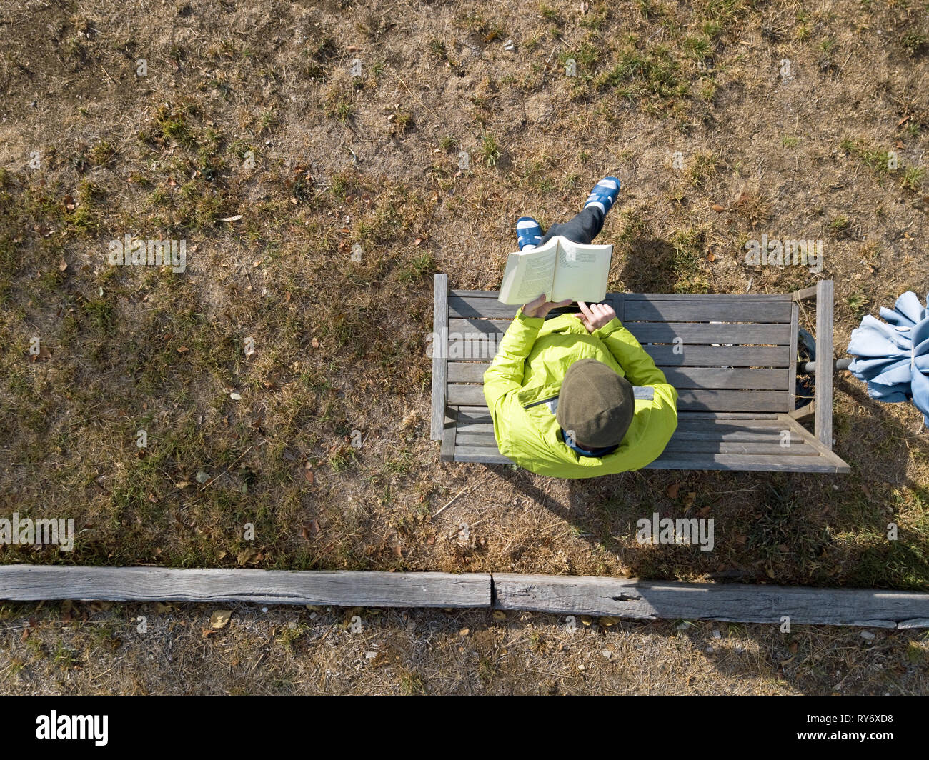 Aerial guy reading book and sitting outdoors with bright jacket and slippers. Aerial photography captured in Victoria, Australia. - Stock Image
