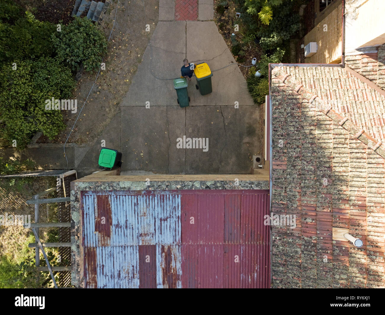 Pensioner active at home aerial view from above, taking the rubbish bins out. Aerial photography captured in Victoria, Australia. - Stock Image