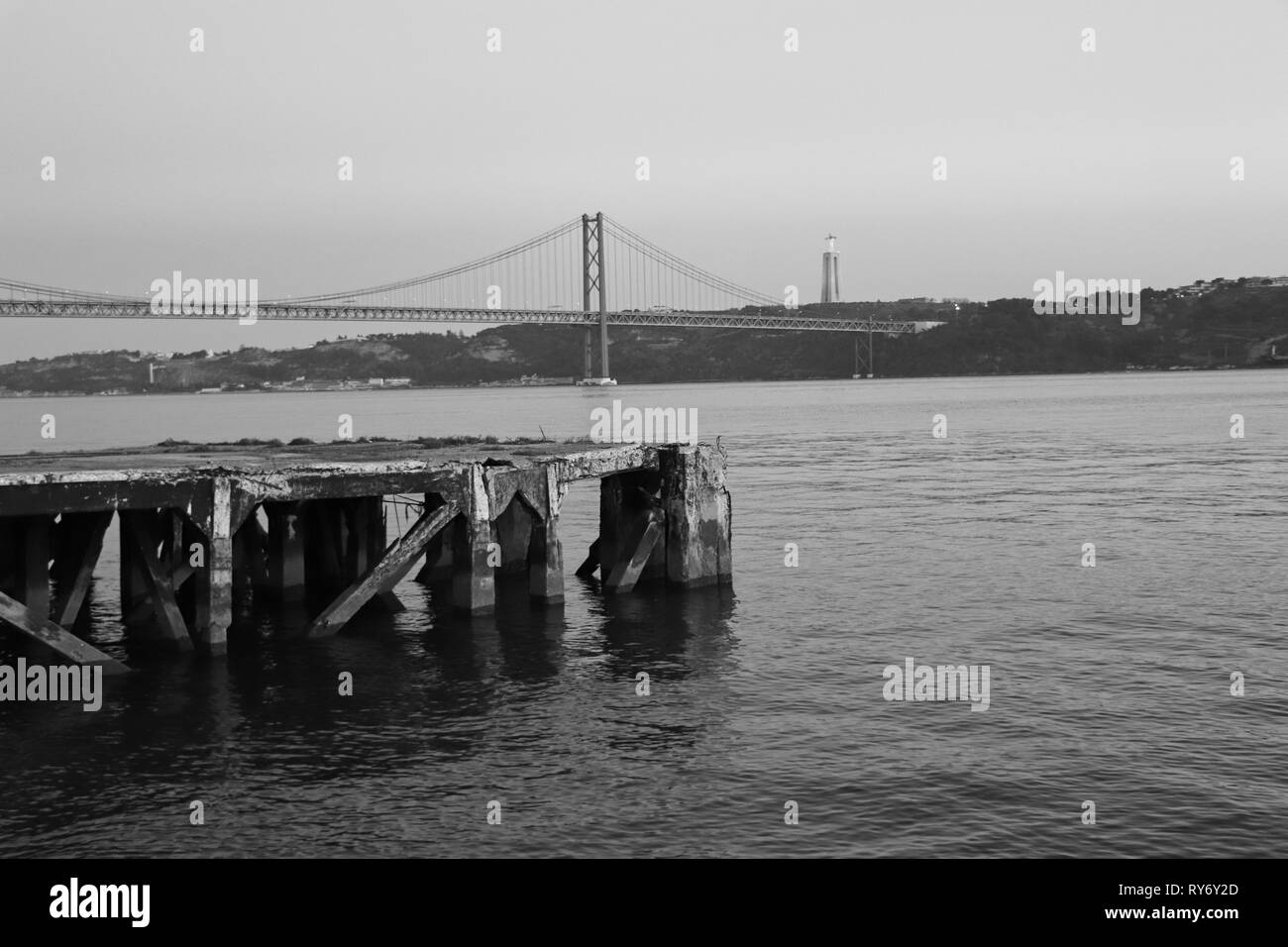 Pier in Lisbon with the 25 of April bridge in background - Stock Image