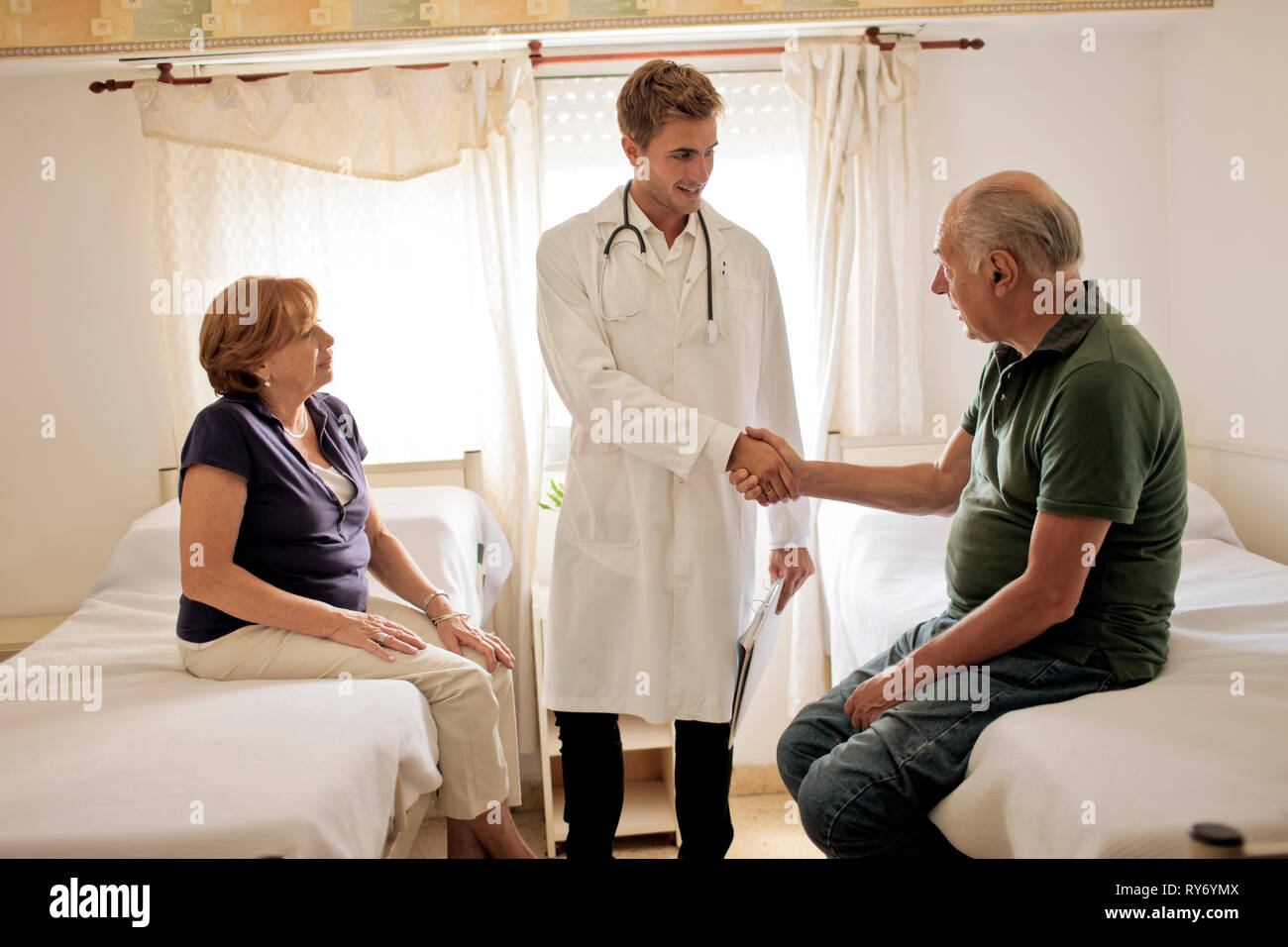 Young doctor greeting female patient and her husband in hospital room. Stock Photo