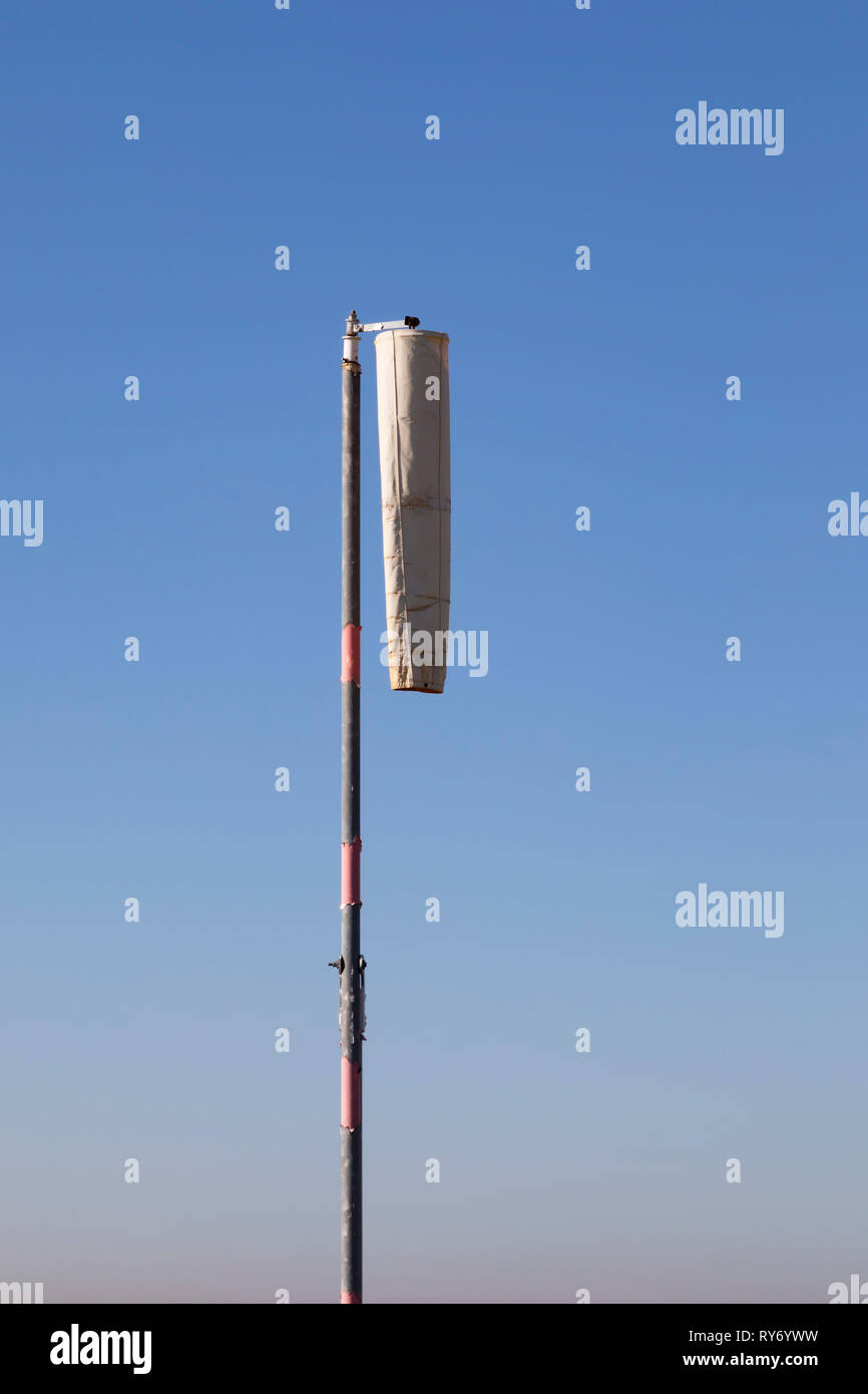 Limp, hanging wind sock in nil wind. - Stock Image