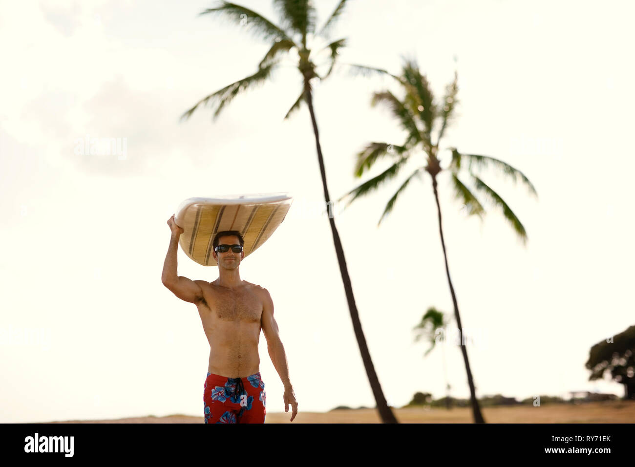 Mid adult man carrying a surfboard on top of his head. Stock Photo