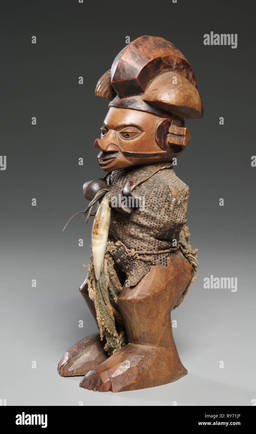 Figure, late 1800s-mid 1900s. Central Africa, Democratic Repulic of the Congo, late 19th-mid 20th Century. Wood, lizard skin, leopard tooth, seed pods, cloth; overall: 23 cm (9 1/16 in - Stock Image