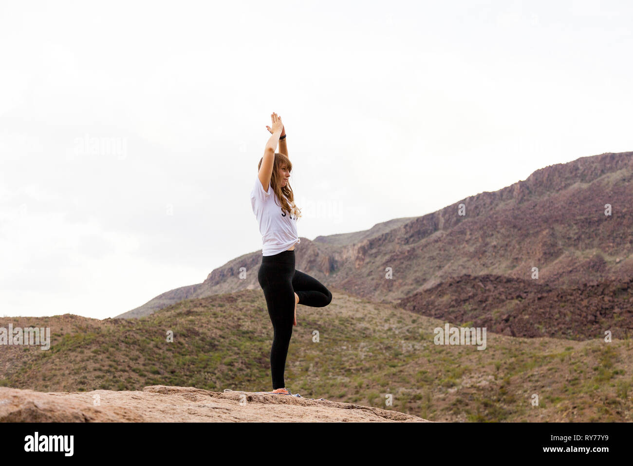 A young woman practices yoga in Big Bend National Park. - Stock Image