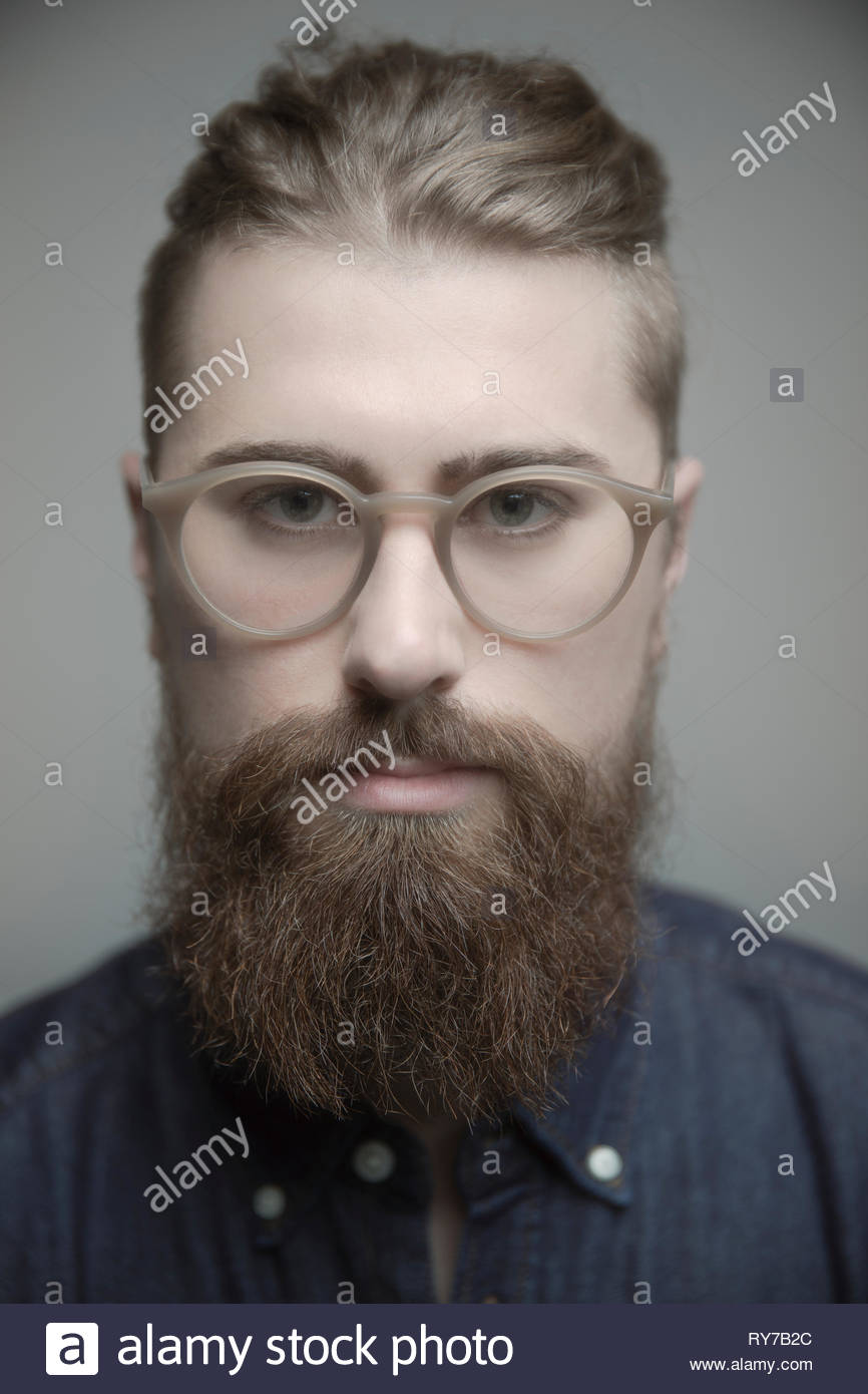 Close up portrait confident handsome young man with eyeglasses and beard - Stock Image