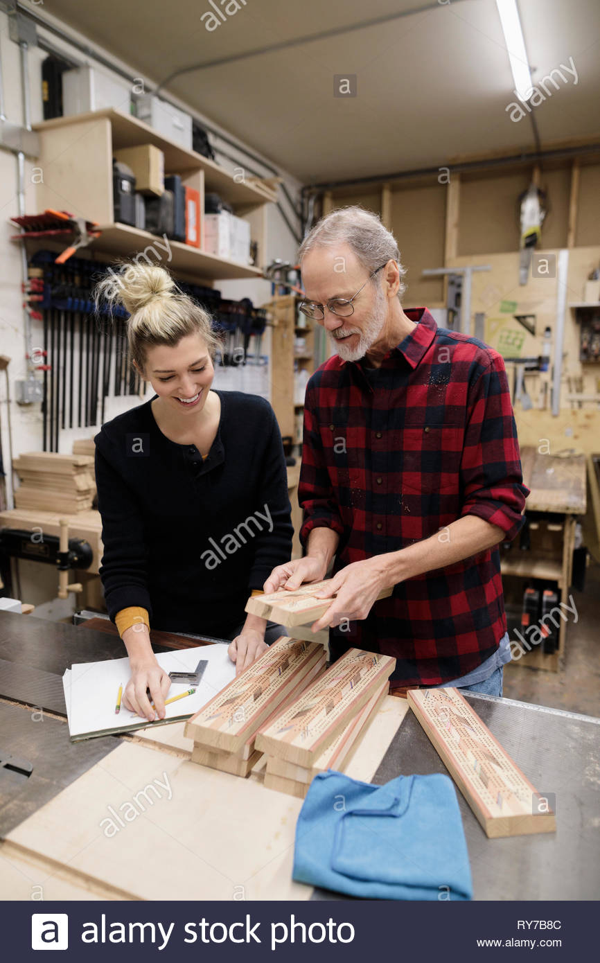 Father and daughter carpenters making cribbage boards in workshop - Stock Image