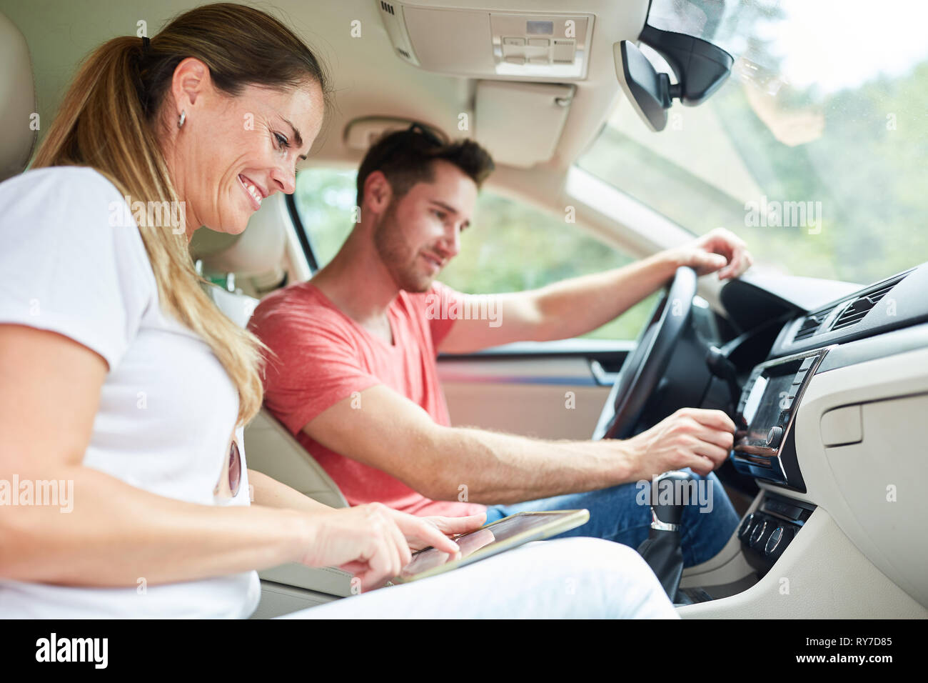 Happy couple driving in car using tablet computer as navigation system - Stock Image