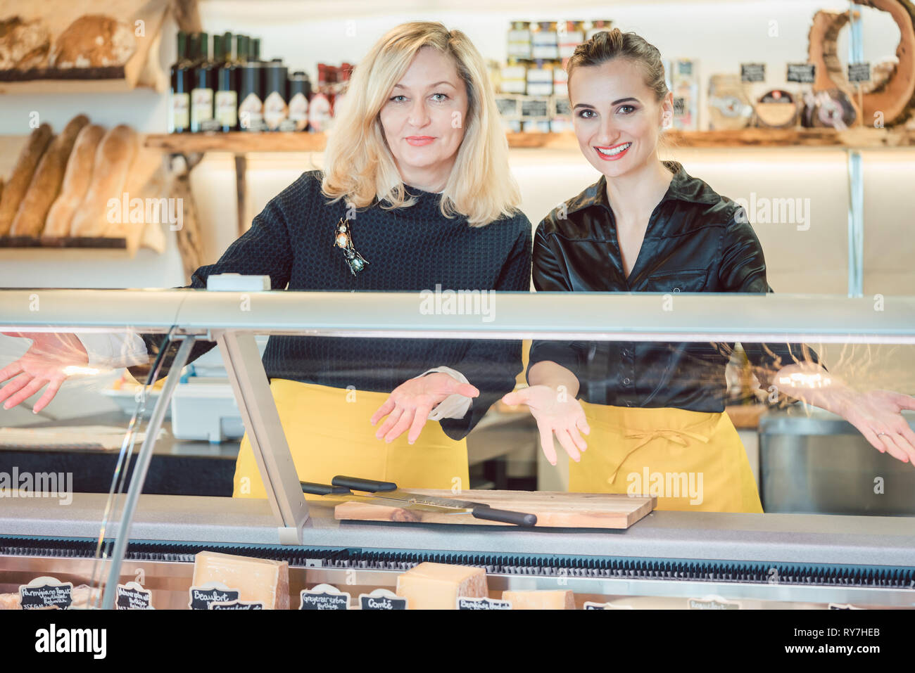 Two salesladies at the cheese counter offering their goods - Stock Image