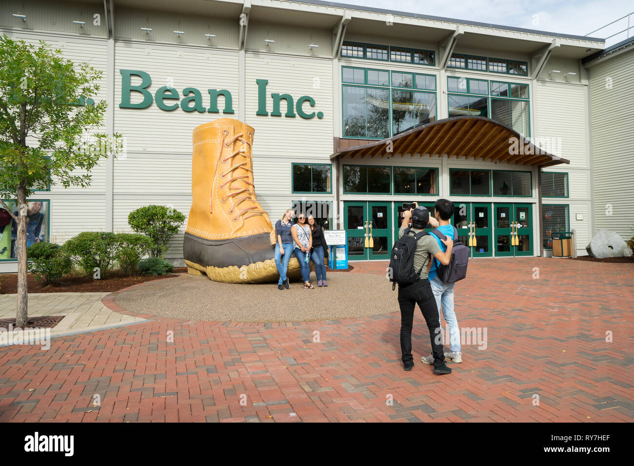 Visitors taking a souvenir picture with the 90th anniversary bean boot in front of LL Bean store in Freeport, Maine, USA. - Stock Image