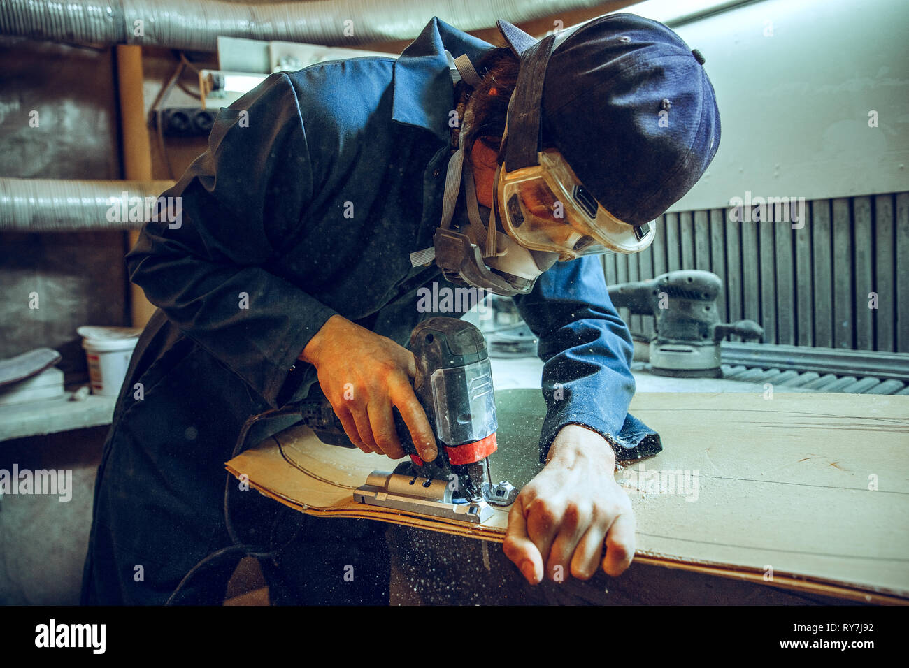 Carpenter using circular saw for cutting wooden boards. Construction details of male worker or handy man with power tools Stock Photo