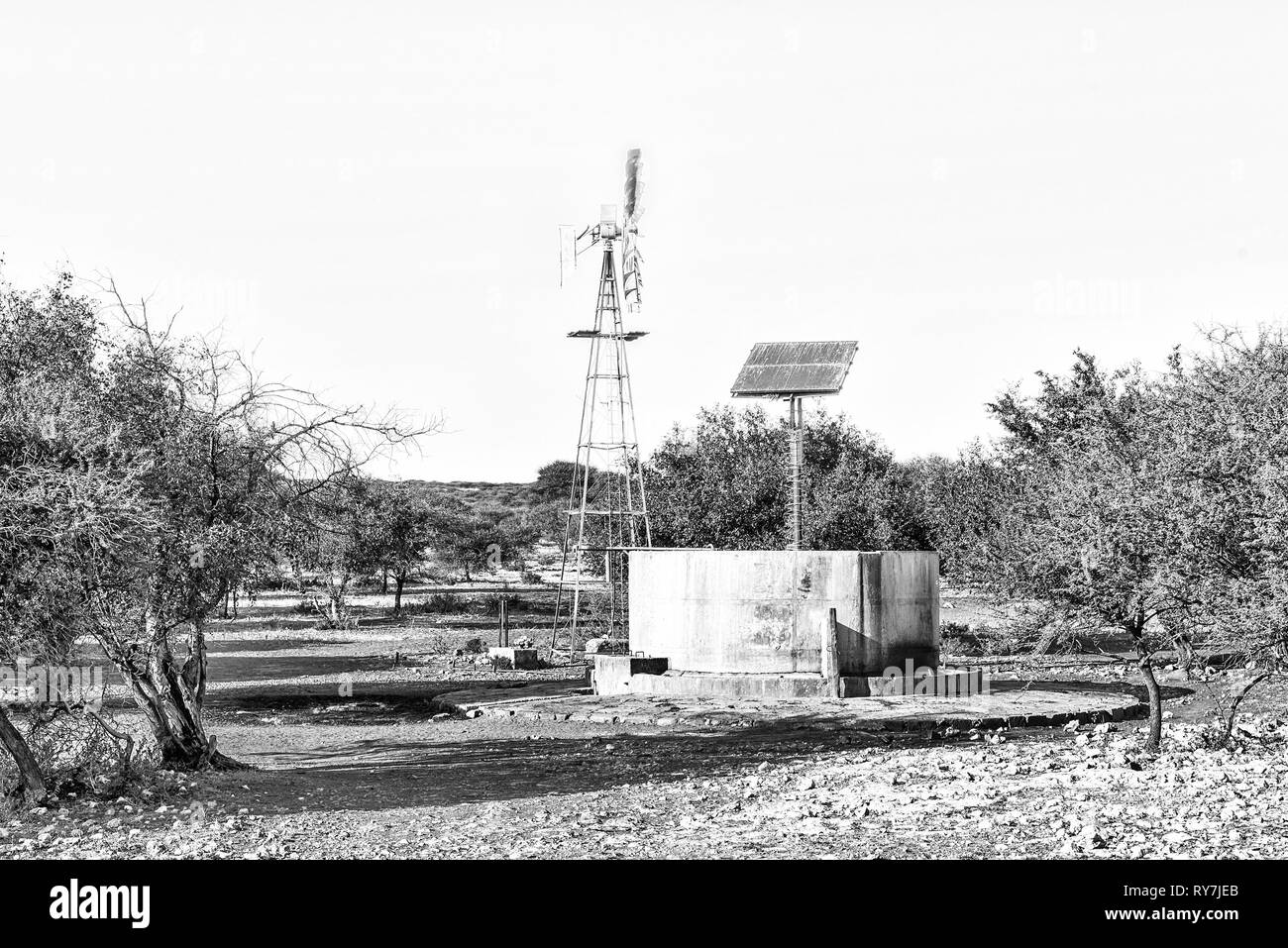 A water-pumping windmill and solar panels for a waterpump near Schmidtsfrift, a village in the Northern Cape Province of South Africa. Monochrome - Stock Image