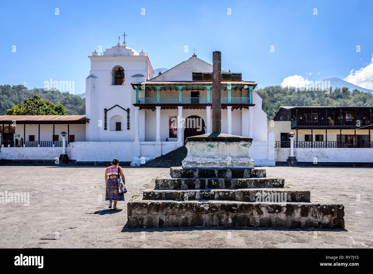 Santiago Atitlan, Lake Atitlan, Guatemala - March 8, 2019: Maya woman walks across plaza to Catholic church in lakeside town in Guatemalan highlands. - Stock Image