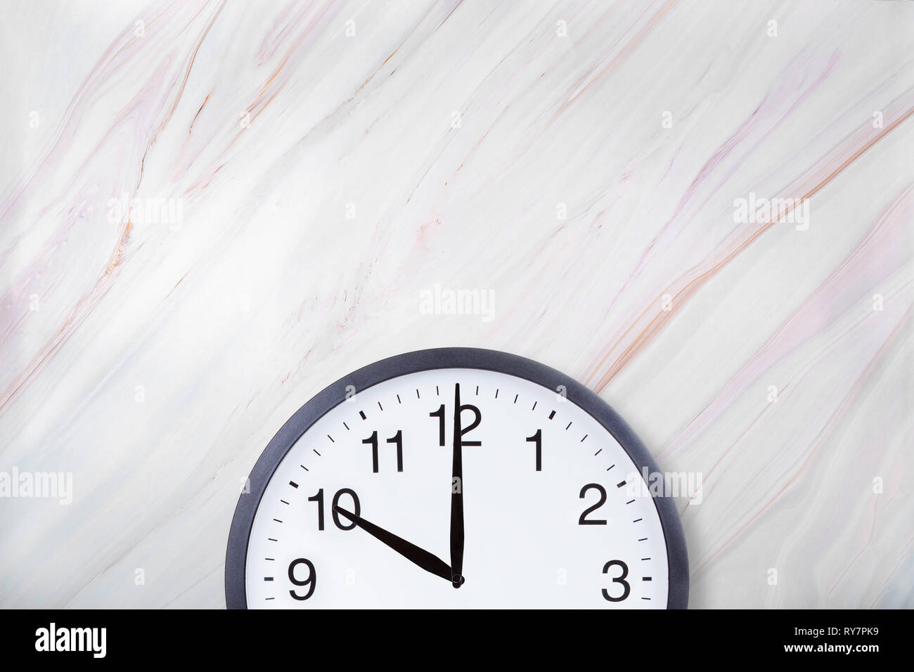 Wall clock show ten o'clock on white marble texture. Office clock show 10pm or 10am - Stock Image