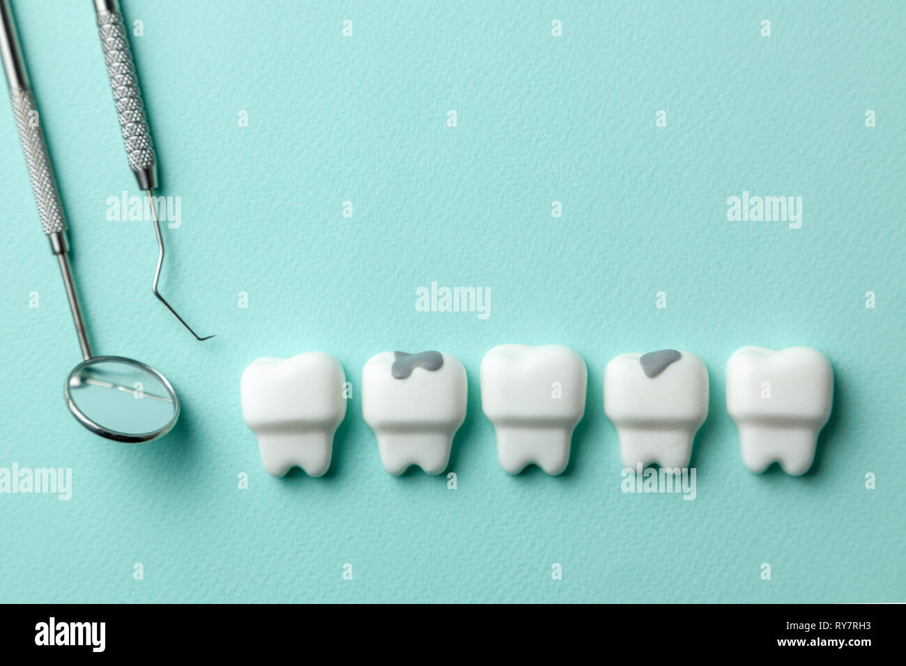 e4a61777a3b6 Healthy white teeth and tooth with caries on green mint background and  dentist tools mirror