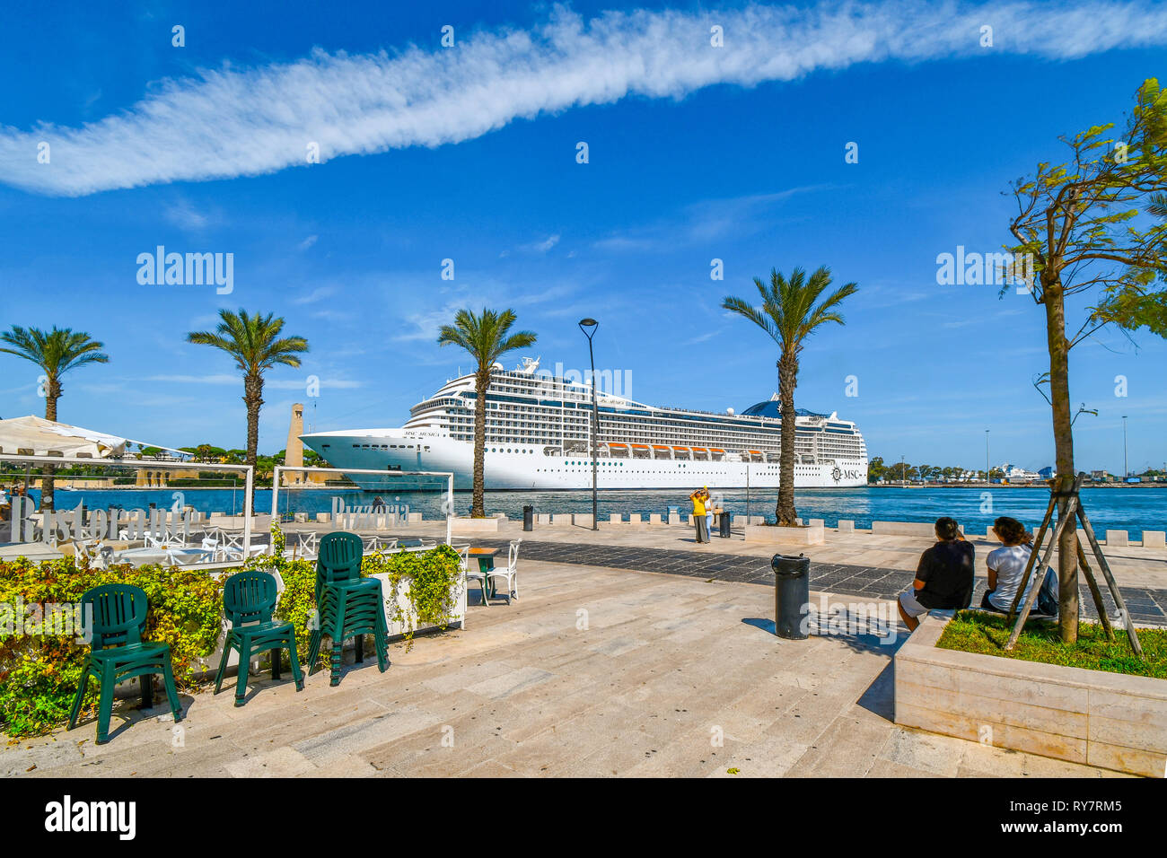 Tourists watch as a massive cruise ship pulls into the narrow port on the Adriatic Sea in the mediterranean city of Brindisi, Italy, in Puglia region - Stock Photo
