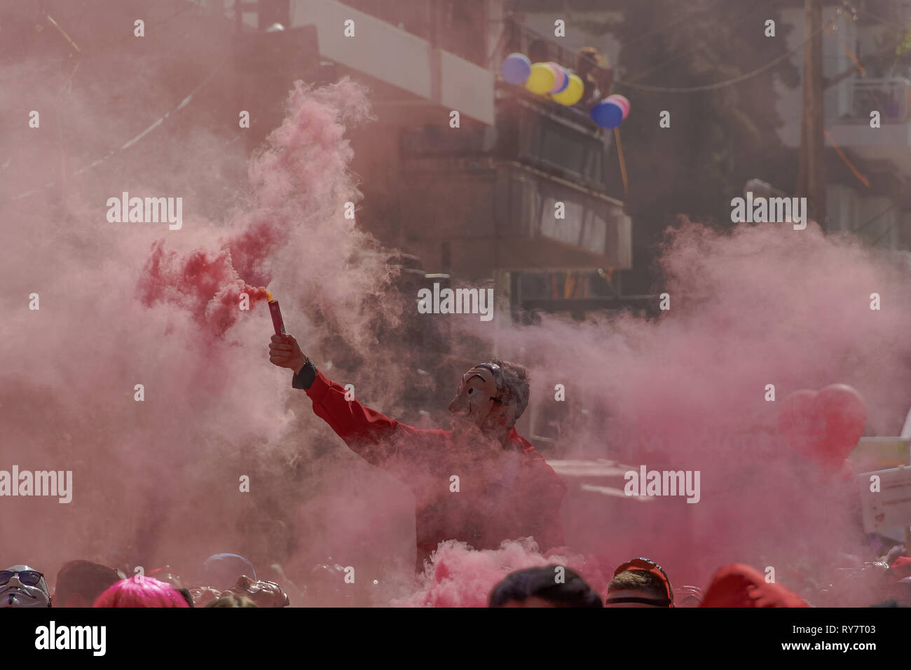 Casa De Papel costume carnival parade participant holds flare. Salvador Dali hoodie red jumpsuit costume person with dense smoke lit flare in Xanthi. - Stock Image