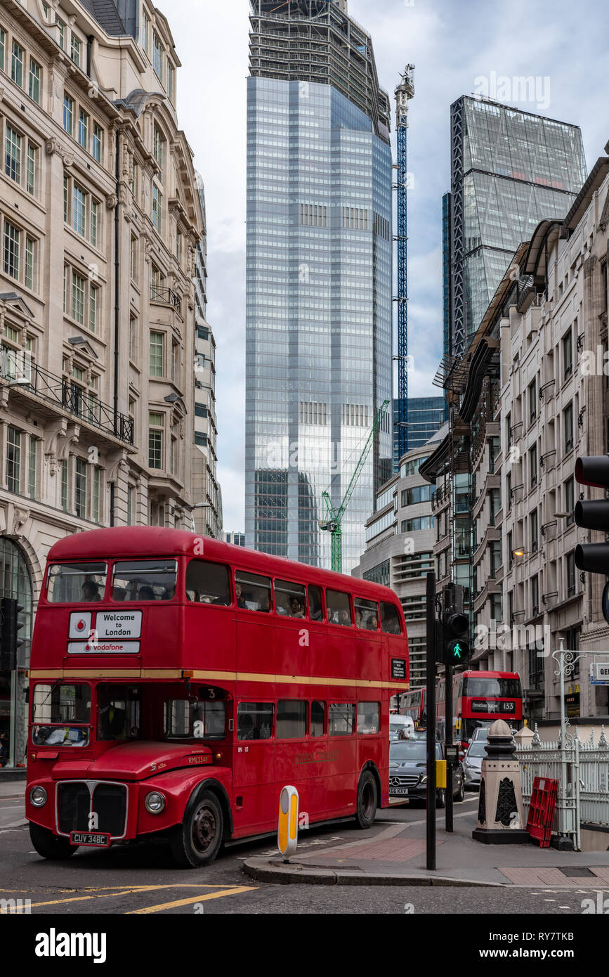 An old London Routemaster bus below the towering finance blocks of the City of London - Stock Image