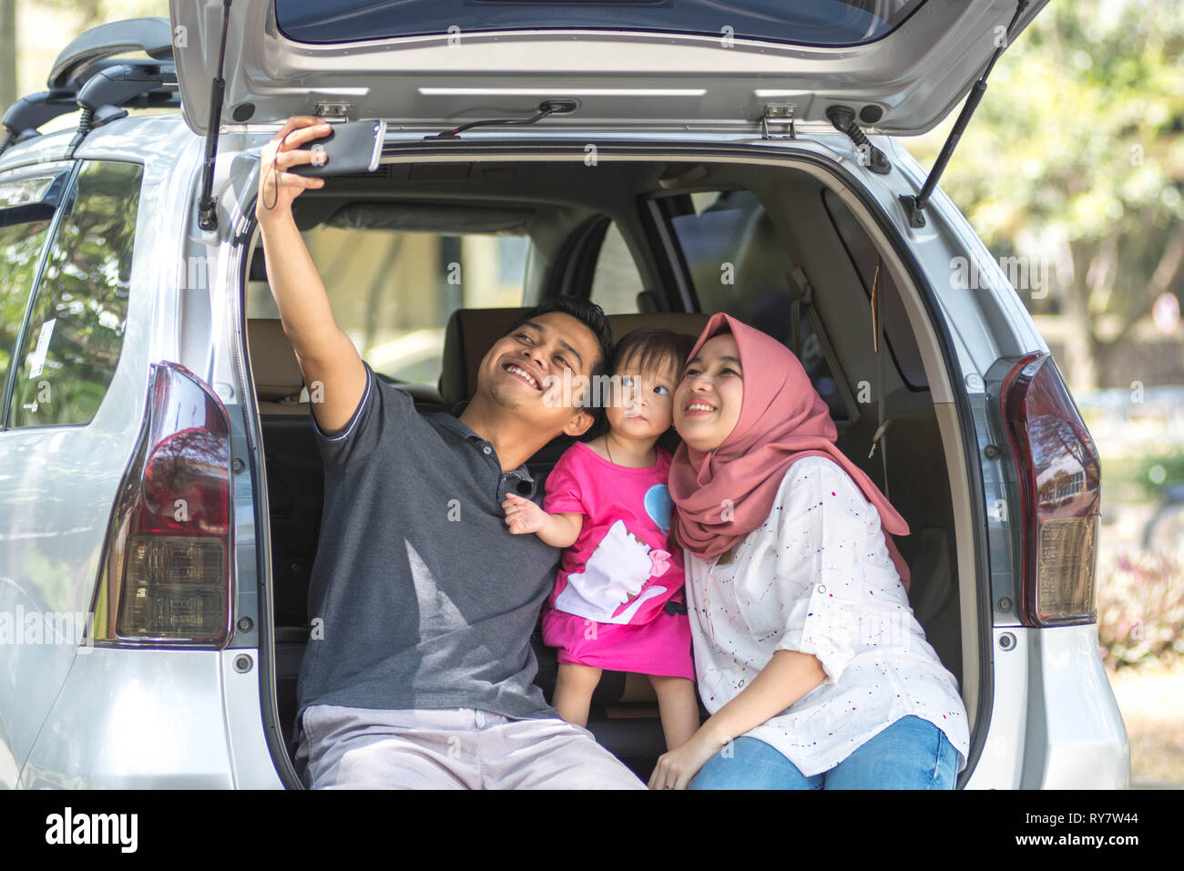 young family , transport, leisure, road trip and people concept - front view of happy man, woman and little girl sitting on trunk of hatchback car and - Stock Image