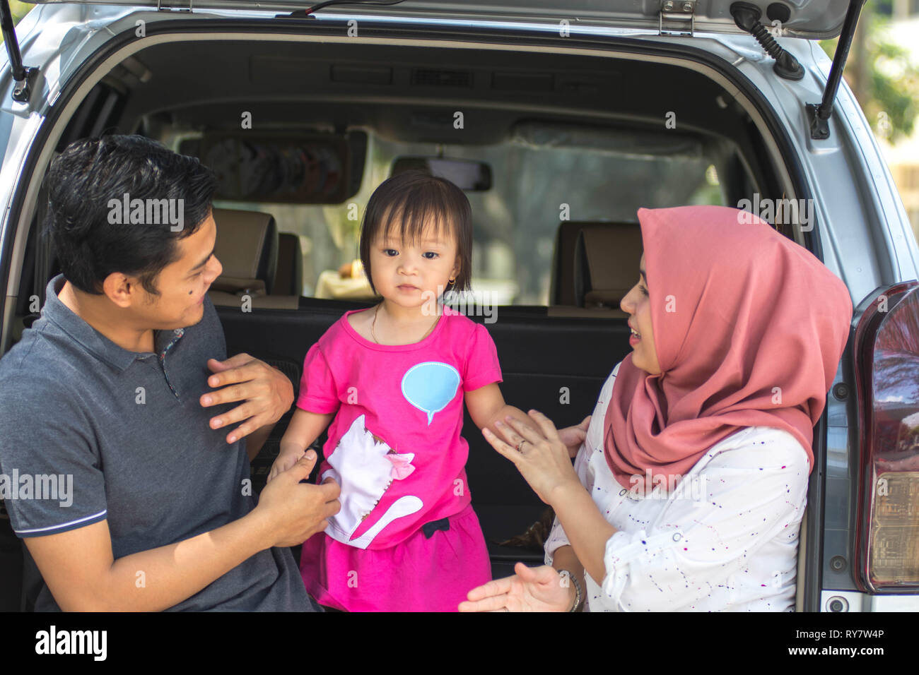 young muslim family , transport, leisure, road trip and people concept - happy man, woman and little girl sitting on trunk of hatchback car and talkin - Stock Image