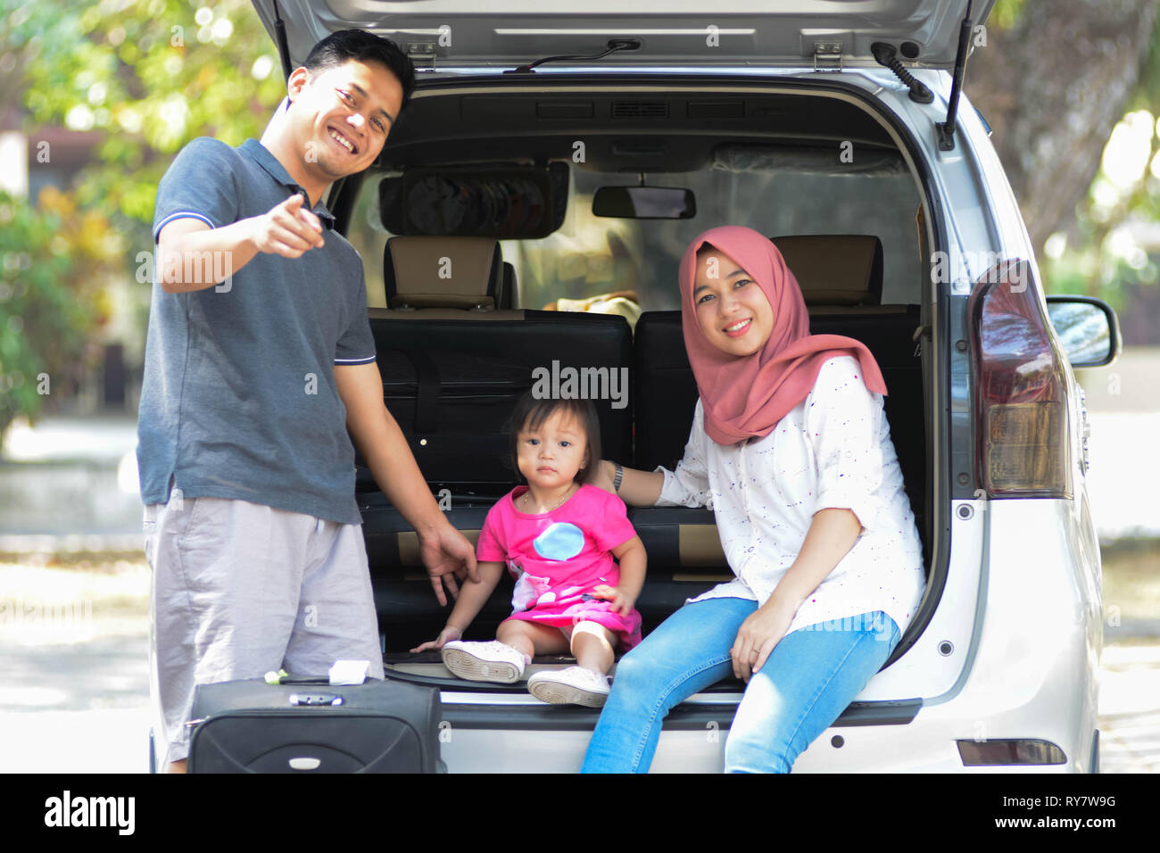 young muslim family , transport, leisure, road trip and people concept - happy man, woman and little girl sitting on trunk of hatchback car and pointi - Stock Image