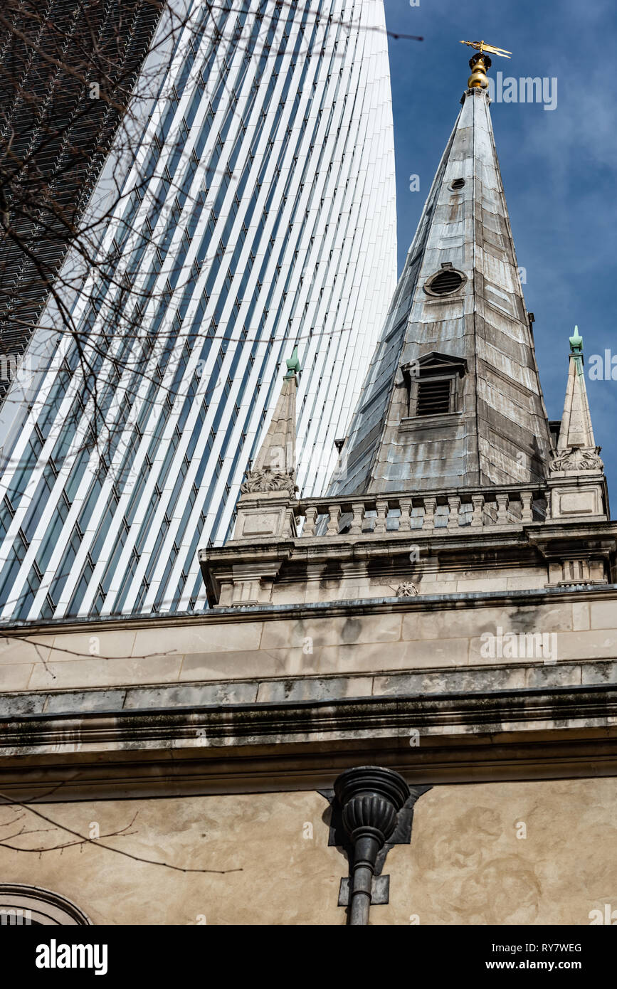 The great mass of glass and steel of the 'Walkie-talkie' building contrasts with the more classical design of St Margaret Patten's Church spire. - Stock Image