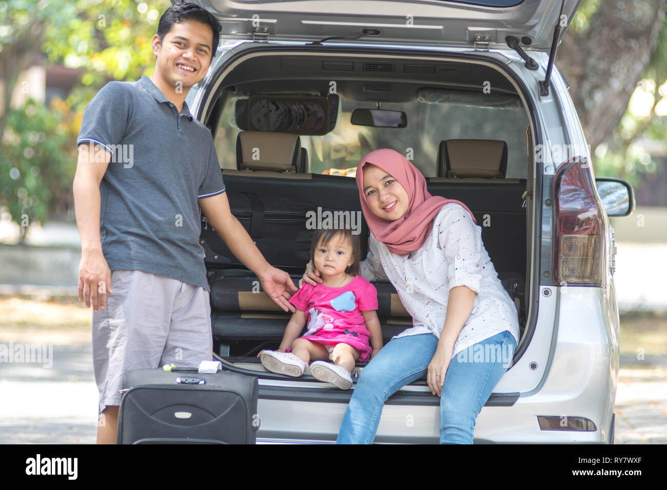 young muslim family, transport, leisure, road trip and people concept - happy man, woman and little girl sitting on trunk of hatchback car and talk - Stock Image