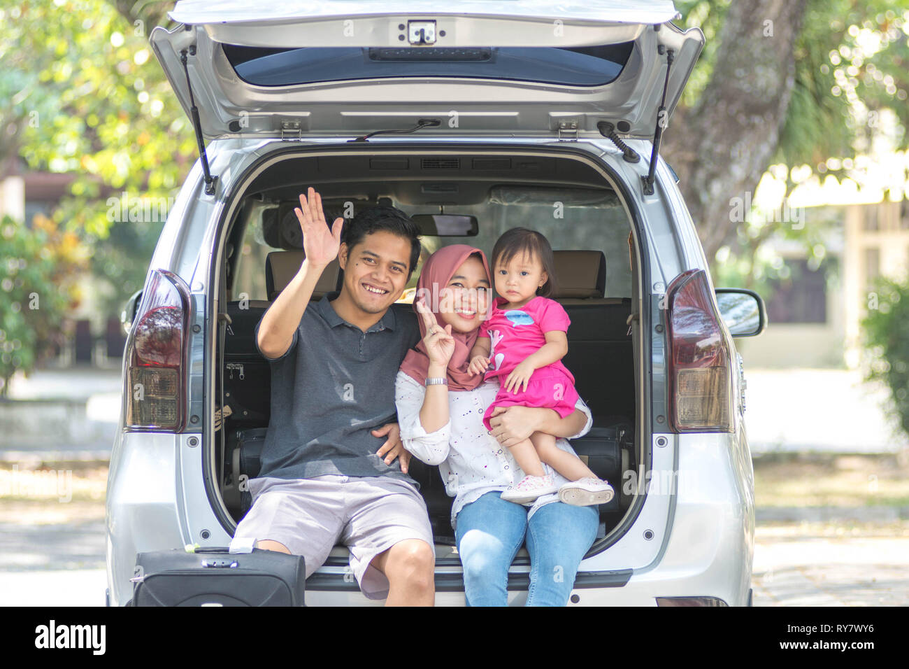 young muslim family, transport, leisure, road trip and people concept - happy man, woman and little girl sitting on trunk of hatchback car and waving - Stock Image