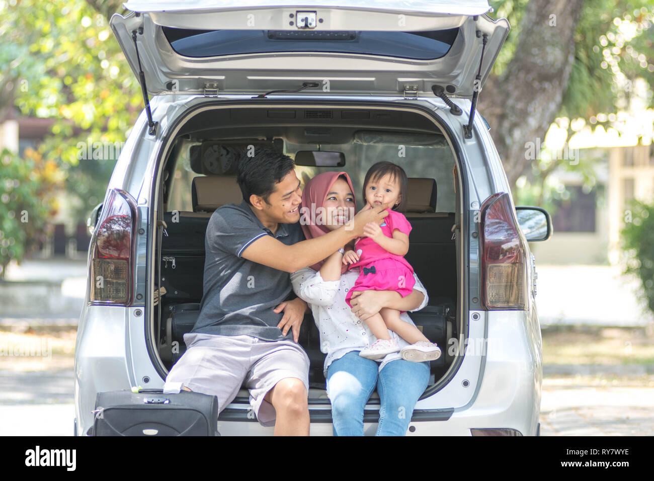 young muslim family , transport, leisure, road trip and people concept - happy man, woman and little girl sitting on trunk of hatchback car and laugh - Stock Image