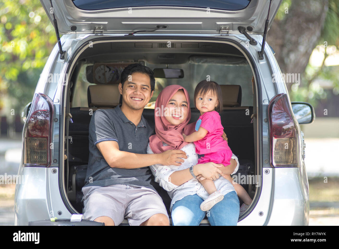 young muslim family , transport, leisure, road trip and people concept - happy man, woman and little girl sitting on trunk of hatchback car and smile - Stock Image