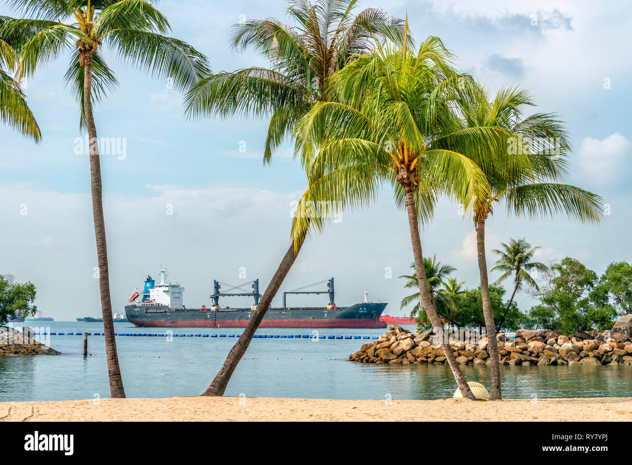Palawan Beach On Sentosa Island With Cargo Ship Moored In