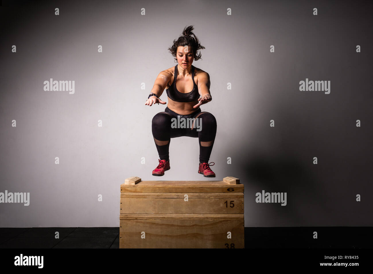 Athletic young lady in sportswear with reached out hands jumping on wooden box in gym on grey background - Stock Image