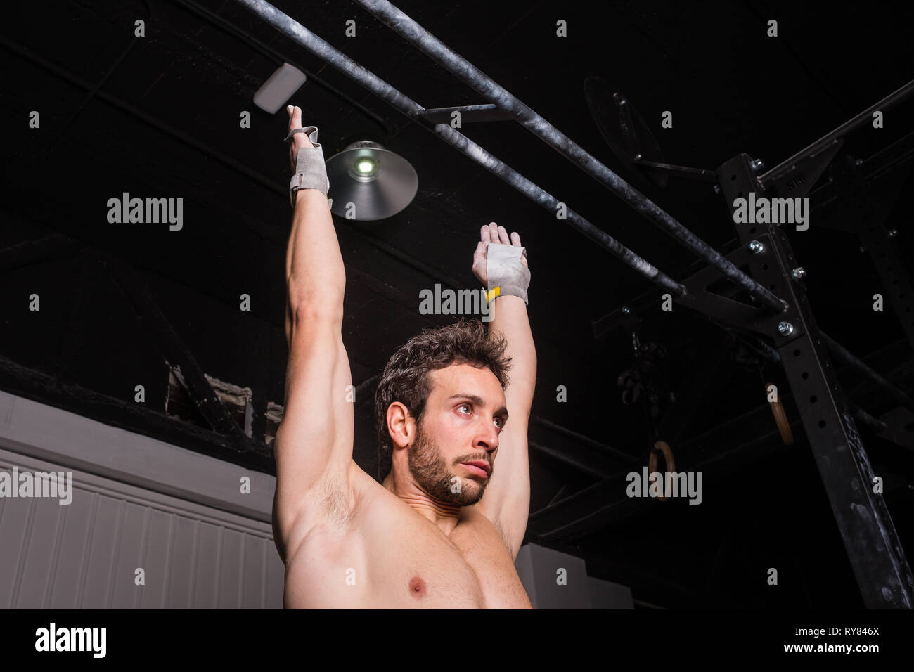 athletic young shirtless guy hanging on bar near wall in gym - Stock Image