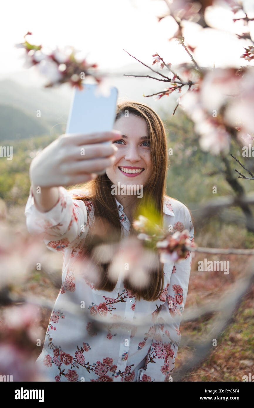 Attractive cheerful lady taking selfie on mobile phone near blooming woods in garden on mountain - Stock Image