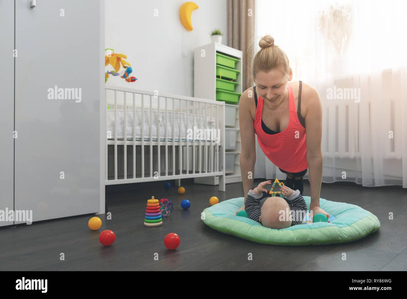 young woman doing push ups at home while playing with her little baby Stock Photo