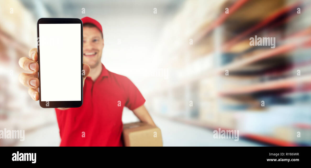 young smiling delivery service courier showing blank smart phone at warehouse. copy space - Stock Image