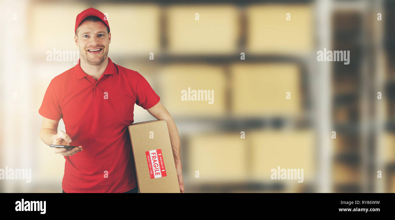 delivery man standing in warehouse holding cardboard box and mobile phone - Stock Image