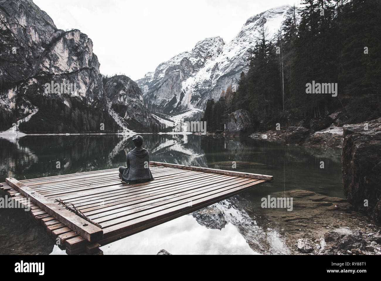 Back view of male sitting on wooden float boat between amazing lake and high stone mountains in Italy - Stock Image