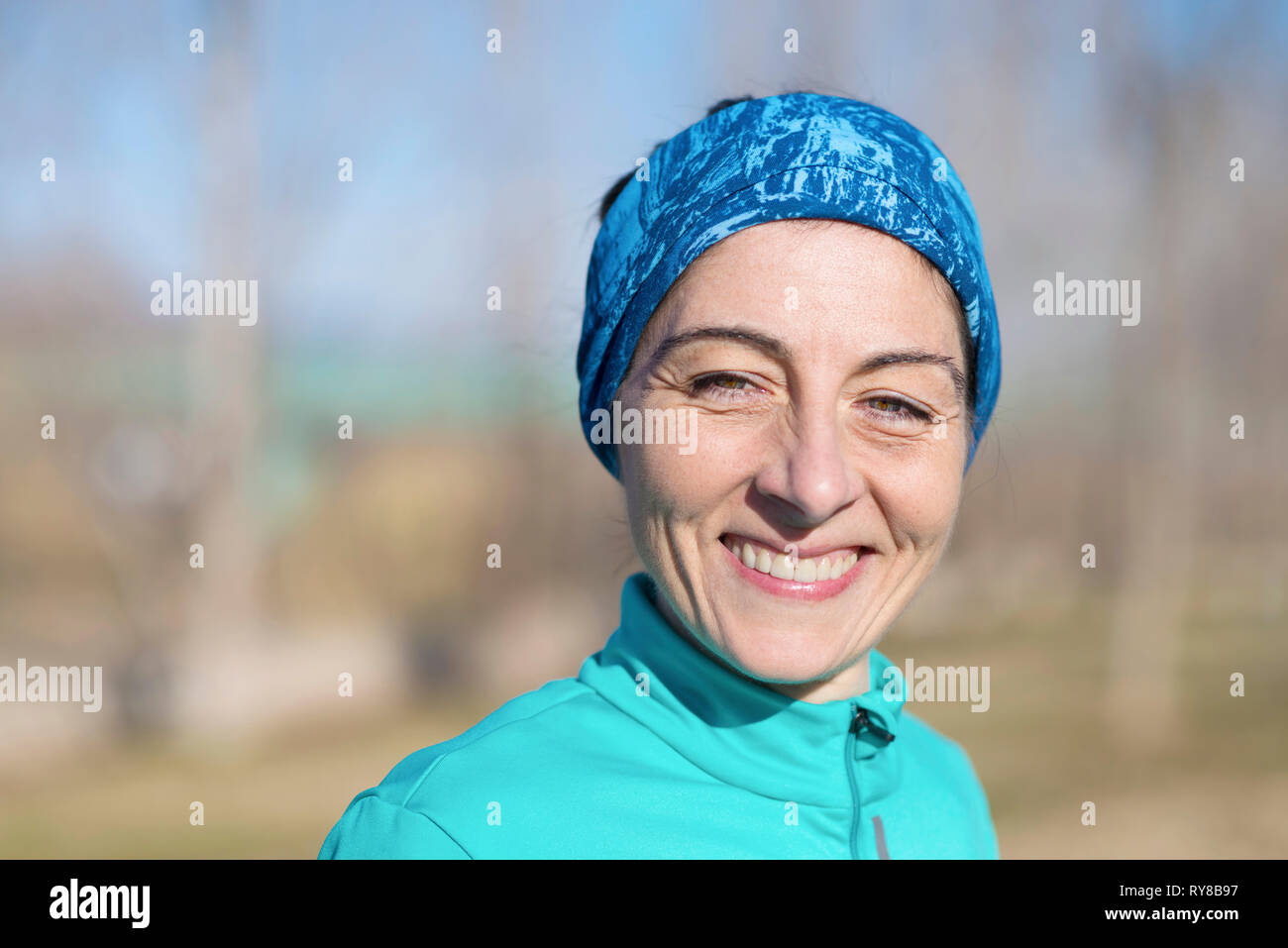 Close-up portrait of smiling female athlete standing in park during sunny day - Stock Image