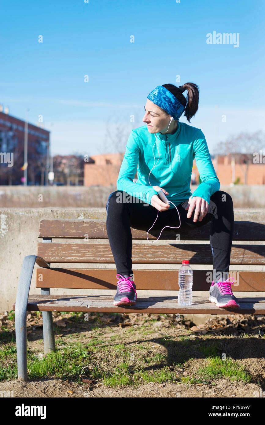 Female athlete listening music while sitting on bench against blue sky at park during sunny day - Stock Image