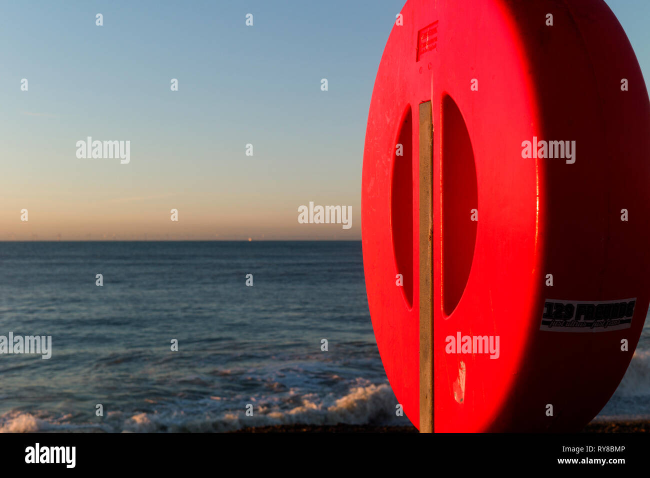 Red life buoy cover on beach, Brighton, UK Stock Photo