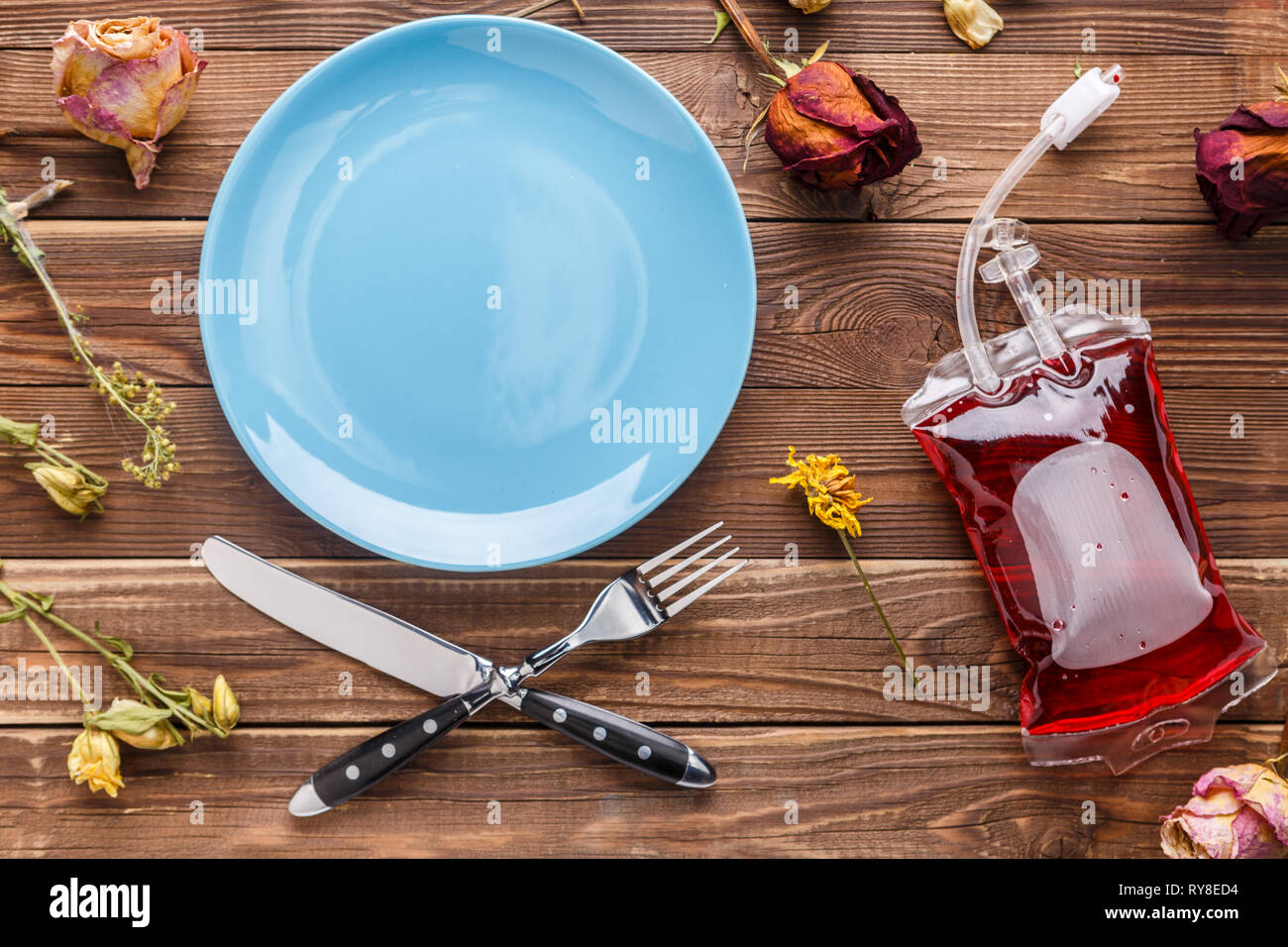 Wooden table with plate,flowers - Stock Image