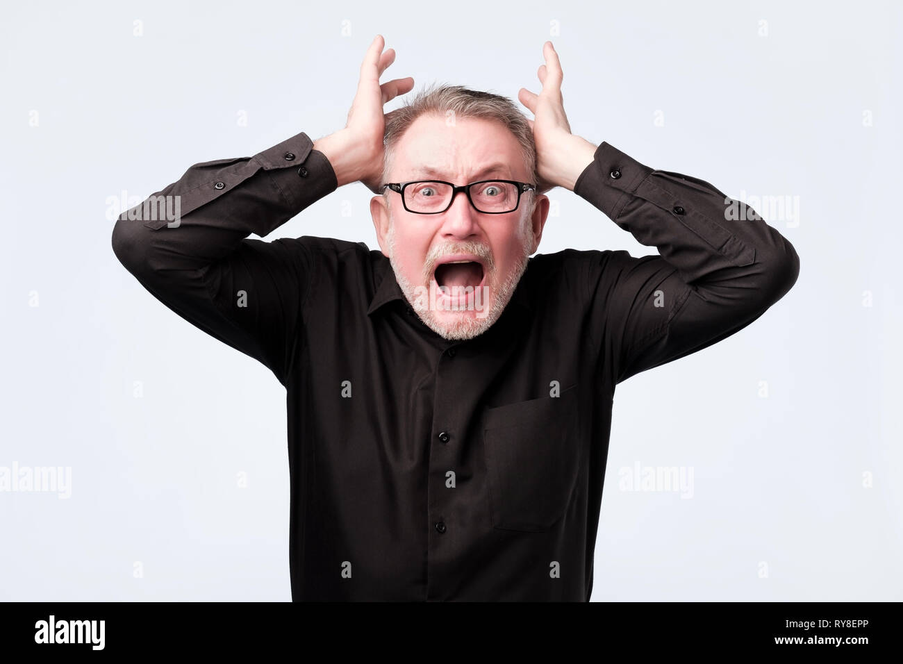 senior man eyes mouth wide open, hands in air yelling screaming shouting - Stock Image