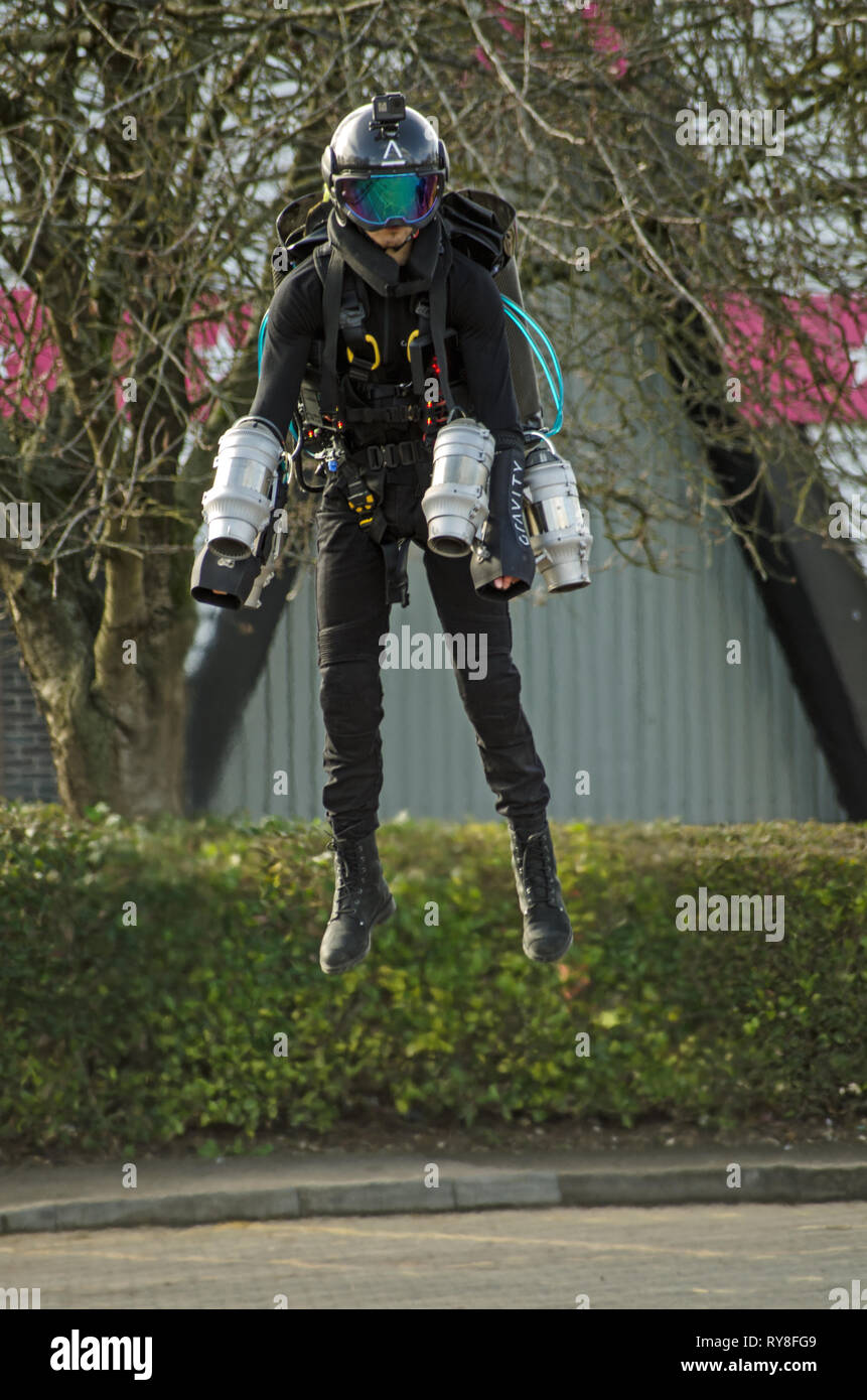 BASINGSTOKE, UK - MARCH 11, 2019: Gymnast turned pilot Ryan Hopgood demonstrating a Gravity Industries jet pack by flying across a car park at Basings - Stock Image
