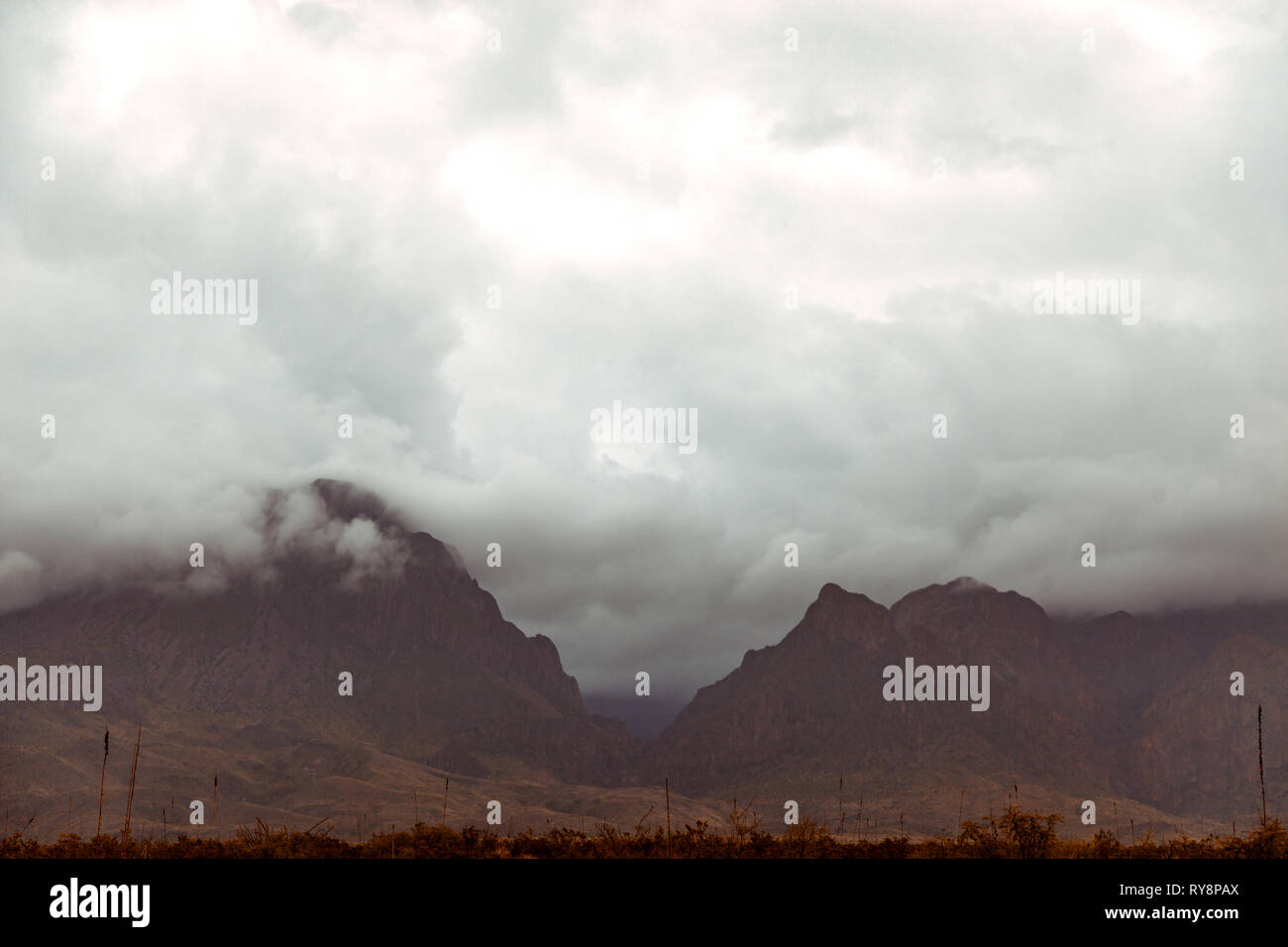 Dark and ominous clouds rolling through the widow of the Chisos Mountains in Big Bend National Park. Stock Photo