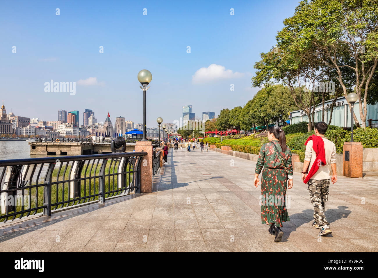 1 December 2018: Shanghai, China - Visitors walking on the bank of the Huangpu River on the Pudong side, opposite The Bund, Shanghai. Stock Photo