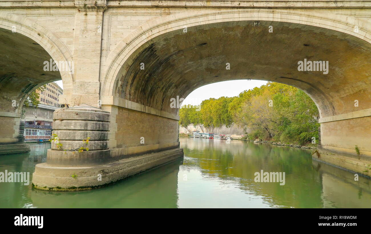 The clear water of the Tiber river in Rome Italy going under the bridge across the river - Stock Image