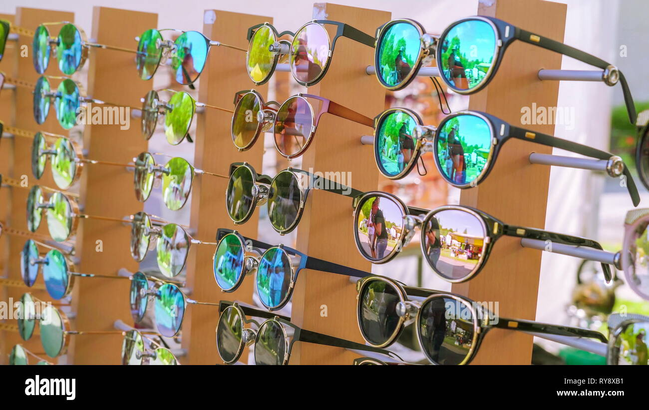 Different variations of sunglasses on the stall being displayed on the sidewalk - Stock Image