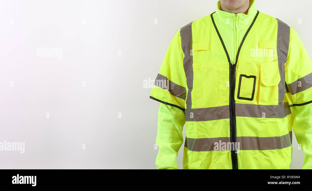 A man with warning safety clothes for roadworks and construction sites. High visibility reflective yellow safety vest. Plenty of copy space for your o - Stock Image