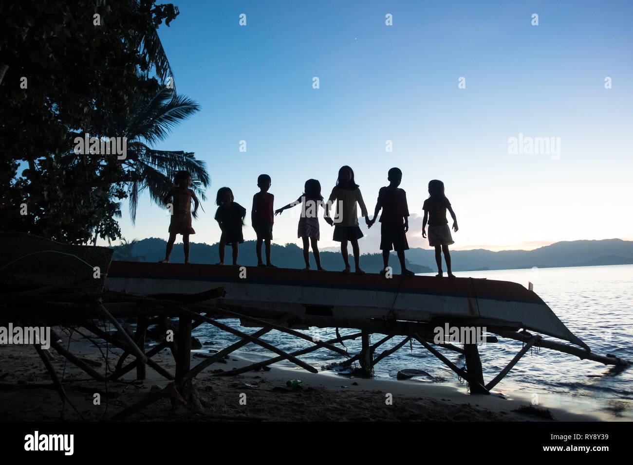Filipino children holding hands on a fishing boat by a sunset sea - Port Barton, Palawan - Philippines - Stock Image